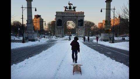 A boy pulls a sled through a snowy Prospect Park in Brooklyn on Saturday.