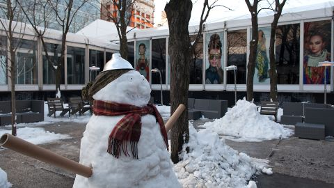 Snowmen made from backstage lamps, paper rolls and water bottle caps stand outside the rest area during Fashion Week in New York on February 10.
