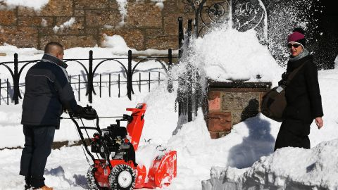 A woman walks past a man clearing snow from a sidewalk on February 10 in Boston.