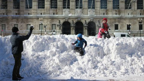 Sean McCullough, left, plays with his children in Copley Square in Boston on Sunday, February 10, following a powerful blizzard. The storm dumped more than two feet of snow in parts of New England.