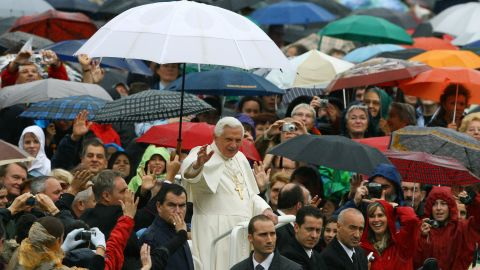 Benedict waves from under an umbrella as he arrives to lead his weekly general audience in Saint Peter's Square at the Vatican in October 2007.
