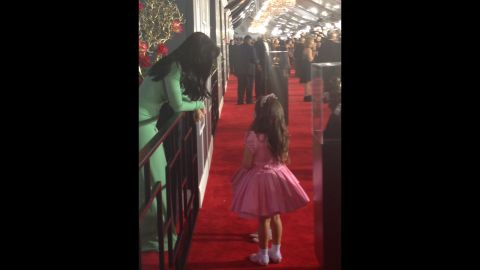 """Katy Perry planned to race past the press like her BFF Rihanna, but couldn't resist stopping for a little girl talk with """"The Ellen Degeneres Show's"""" pink princesses Sophia Grace and Rosie (obscured in photo). What do you think they're talking about?"""