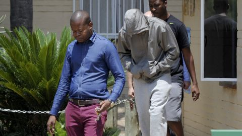 Pistorius leaves a police station with his face covered in February 2013.