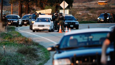 Police search cars at a blockade as they come down off the mountain during a manhunt for Dorner on February 12.
