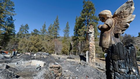 A statue of an angel stands on a wood column in front of the burned cabin on February 15.