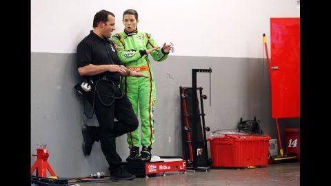 Patrick speaks to a crew member in the garage at Daytona International Speedway in 2012.