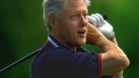 """President Bill Clinton watches as his first tee shot heads off the course and into the trees during a round of golf at the Farm Neck Golf Club of Martha's Vineyard during a family vacation on August 23, 1999. He took a second shot and it landed in the same area. Clinton was known for taking Mulligans, a do-over shot in a friendly match. The press even coined a term for them -- """"Billigans."""""""