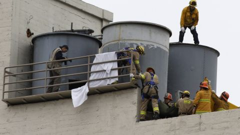 A team works to remove the body. The body of Elisa Lam, 21, of Vancouver, Canada was found in the Cecil Hotel's rooftop water tank by a maintenance worker who was trying to figure out why the water pressure was low on Tuesday.