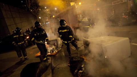 Firemen extinguish a bin on fire during a riot after a march by thousands of people.