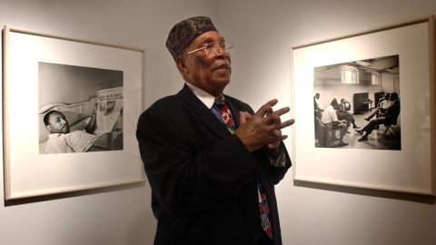 Photographer Ernest Withers stands in front of his photographs at an exhibit at the Art Institute of Philadelphia in 2003.