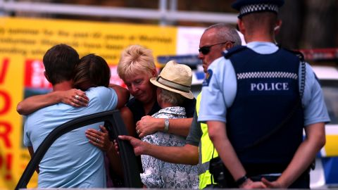 People grieve outside the Muriwai Surf Lifesaving Club after a swimmer died in a fatal shark attack on February 27.