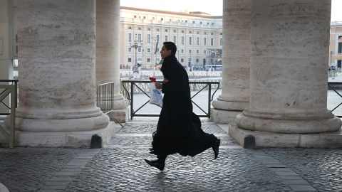 A priest runs to get into St. Peter's Square ahead of pope's last public audience address.