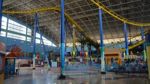 An 1,814-foot rollercoaster is the center of an indoor amusement area, where staff can be found half asleep on counters as they wait for customers.