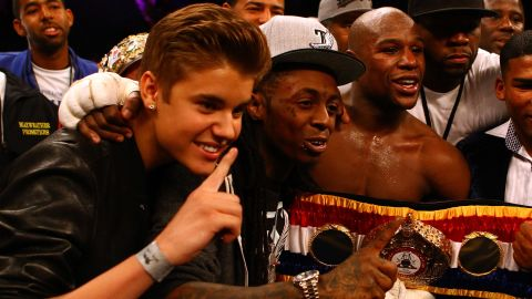 """Bieber makes his bread and butter as a teen pop phenom, but his social circle is wide. His <a href=""""http://sportsillustrated.cnn.com/multimedia/photo_gallery/1205/floyd-mayweather-justin-bieber/content.1.html"""">appearance as part of boxer Floyd Mayweather Jr.'s entourage</a> at a fight in May 2012 had everyone doing a double take. Lil Wayne and 50 Cent were also on hand."""