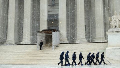 Workers use shovels and brooms to remove a heavy mixture of snow and ice from the west front of the U.S. Supreme Court on March 6.