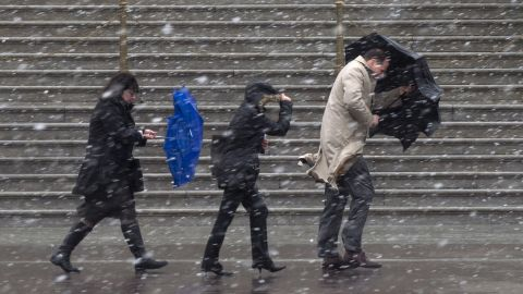 """People walk as snow falls at the U.S. Capitol in Washington on Wednesday, March 6. A winter storm that set snowfall records in Chicago arrived in the capital region early Wednesday, shutting down federal offices and schools. It's been dubbed """"snowquester,"""" a play on the recent forced spending cuts in government."""