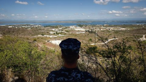 """A Navy sailor surveys the base in October 2009. In December 2013, Congress <a href=""""http://politicalticker.blogs.cnn.com/2013/12/26/obama-signs-budget-defense-bills-in-hawaii/"""" target=""""_blank"""">passed a defense-spending bill</a> that makes it easier to transfer detainees out of the facility."""