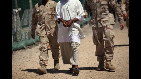 US military guards move a detainee inside the detention center in September 2010. At its peak, the detainee population exceeded 750 men.