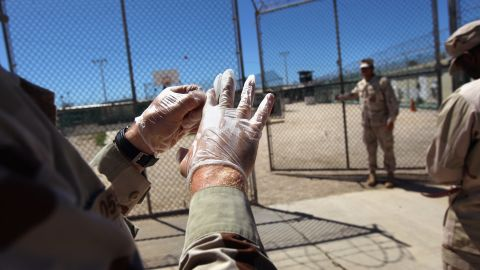 A military guard puts on gloves before moving a detainee in September 2010.