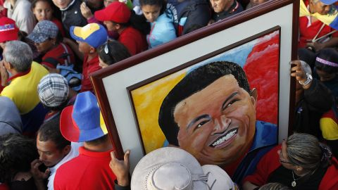 Supporters of Chavez hold a portrait of him as they wait for a chance to view his body lying in state, at the military academy in Caracas on March 8.