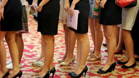 Young Chinese women stand in line to be interviewed for flight attendant jobs in China's Anhui province.