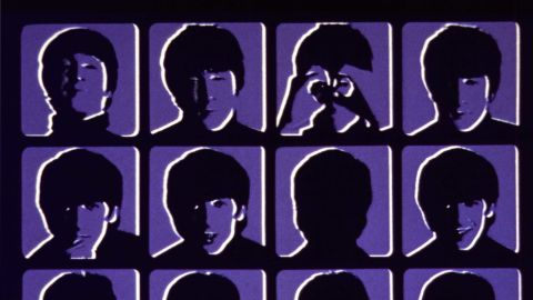 """The original UK cover of the Beatle's third album, """"A Hard Day's Night,"""" in blue. Four rows of four head shots of each Beatle with different facial expressions are set up as frames from a movie."""