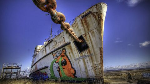 """The first paintings to appear were of orange and blue pirates on the ship's bow, created by Latvian artist <a href=""""http://thekiwie.com/"""" target=""""_blank"""" target=""""_blank"""">KIWIE</a>. Each pirate is nine meters tall and includes the dates the ship was built (1956) and docked in Llanerch-y-Mor (1979)."""