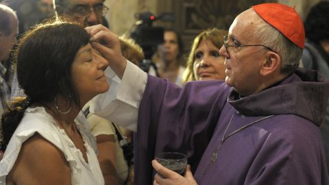 Bergoglio, right, draws the cross on the forehead of a parishioner during a Mass for Ash Wednesday, which begins the 40-day period of abstinence for  Christians before the Holy Week and Easter, on February 13 at the Metropolitan Cathedral in Buenos Aires.