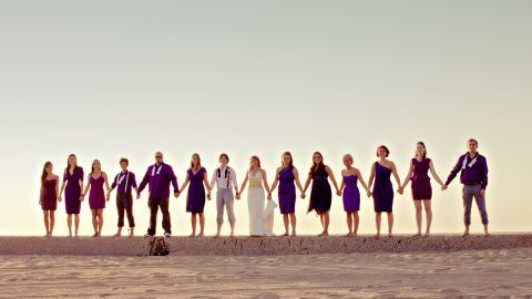 """Group shots can be overly posed or dryly composed, but they don't have to be. The image chosen for the book's cover """"offers the simplicity of the horizon and the steadfast strength of community,"""" Hamm says. From the mix of attire styles and colors, this gender-blended wedding party shows unwavering unity amid the embrace of individuality."""