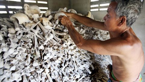 Cambodian Sao Phen prepares skulls and bones of victims of the Khmer Rouge inside a stupa in Kandal province in 2009.