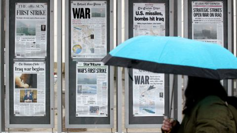 A pedestrian looks at front-page headlines on display outside the future site of the Newseum in Washington on March 20, 2003.