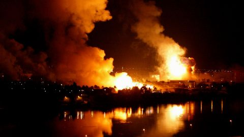 Smoke and flames rise from the riverside presidential palace compound in Baghdad after a massive airstrike on March 21, 2003.
