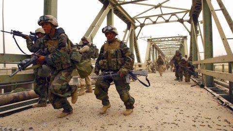Members of the 3rd Battalion, 4th Marines, storm Diyala Bridge in Baghdad on April 7, 2003.