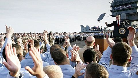 """Sailors applaud as President Bush addresses the nation aboard the USS Abraham Lincoln on May 1, 2003. Standing beneath a banner that read """"Mission Accomplished,"""" the president declared major fighting over in Iraq and called it a victory in the ongoing war on terrorism."""