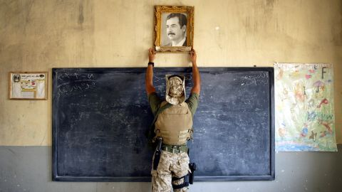 A U.S. Marine pulls down a picture of Saddam Hussein at a school in Al-Kut on April 16, 2003.