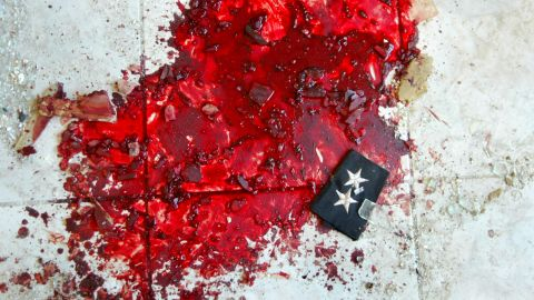 An Iraqi police lieutenant's stars lie in a puddle of blood after a car bombing that targeted a police station in Baquba on November 22, 2003.