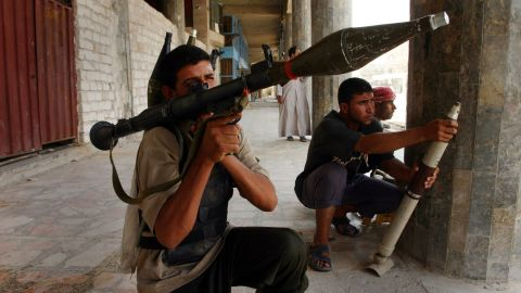Shiite militia members prepare to fire during clashes with U.S. forces in Najaf on August 7, 2004. It was the third day of continuous fighting in the holy city.