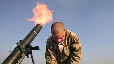 """Spc. Franklin Smith pulls away as a mortar blast is fired from the edge of the U.S. airbase in Tal Afar on January 17, 2005. U.S. teams would frequently fire """"harassment and interdiction"""" mortar fusillades toward suspected enemy positions."""