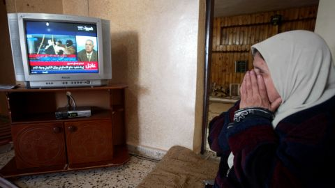 A Palestinian woman watches the news of Saddam Hussein's execution at her home in the West Bank town of Jenin on December 30, 2006. Hussein was hanged for his role in the 1982 Dujail massacre, in which 148 Iraqis were killed after a failed assassination attempt against the then-president.
