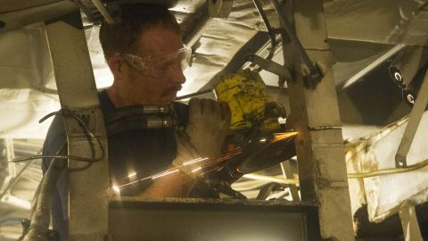 Brandon Berry grinds through steel in the engine room in preparation for removing machinery.