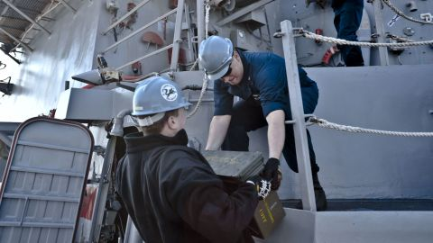 Fire Controlman 2nd Class Jason Titcombe, left, hands Fire Controlman 2nd Class Joshua Clements ordnance aboard the destroyer USS Lassen in this Navy handout photo taken on March 5.