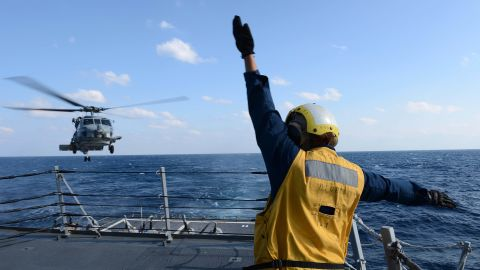 U.S. Navy Boatswain's Mate 3rd Class Brittany Chiles signals to an SH-60B Seahawk helicopter as