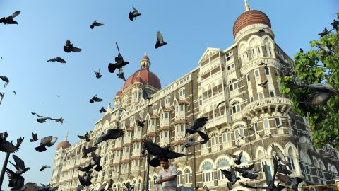 An Indian man (C) feeds pigeons outside the Taj Mahal Palace hotel on the second anniversary of the November 2008 terror attacks in Mumbai on November 26, 2010.