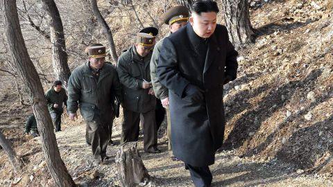 Kim, with North Korean soldiers, makes his way to an observation post in March 2013.
