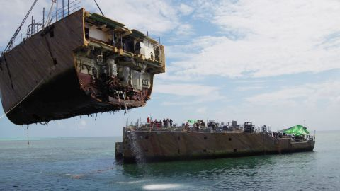 A crane vessel lifts the bow of the USS Guardian on Tuesday, March 26.