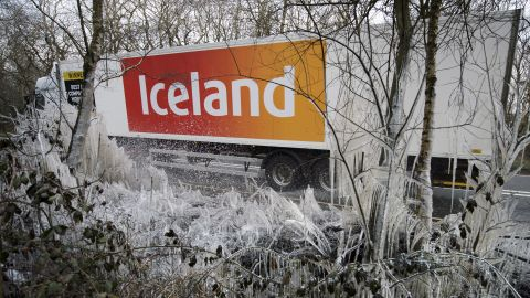 A supermarket semi-truck passes icicles and ice-covered shrubs near Hazeley Bottom, England, south of Reading, on Wednesday, March 27.