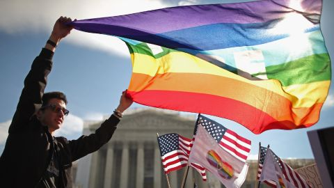 George Washington University student Eric Breese waves a rainbow flag outside the court Wednesday.
