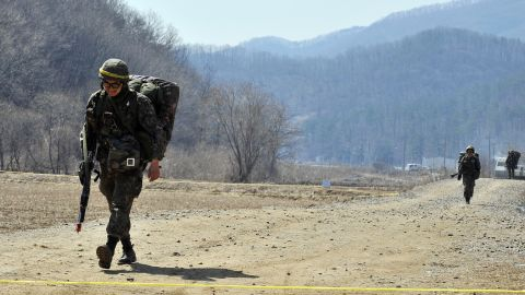 Armed South Korean soldiers walk on a road near a military drill field in Paju on March 27.