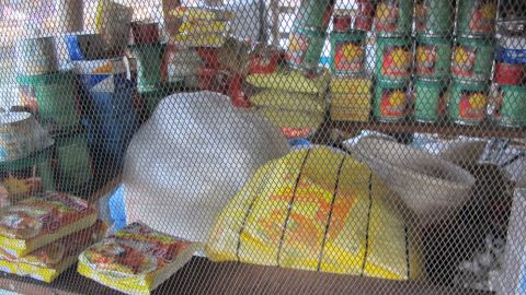 Through a wired screen sit convenience items in this Makoko-style corner store. Instant noodles, rice, canned goods, fruits and vegetables are all on sale in a structure that also houses a family.