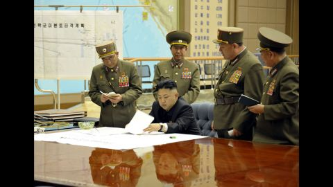 """Kim is briefed by his generals in this undated photo. On the wall is a map titled """"Plan for the strategic forces to target mainland U.S."""""""